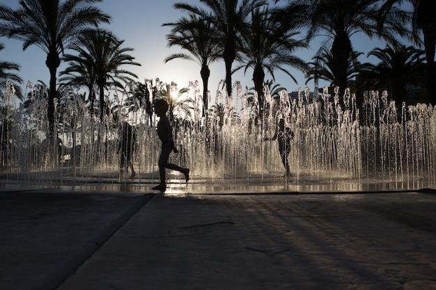 Schattenbild einer gruppe von kindern, die in einem wasserbrunnen spielen