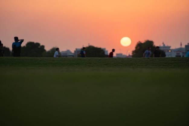 Schattenbild einer gruppe von kindern, die spaß haben, fußballfußball während des dramatischen sonnenuntergangs mit sonnenscheibe spielend zu spielen. aspire park, doha, katar.