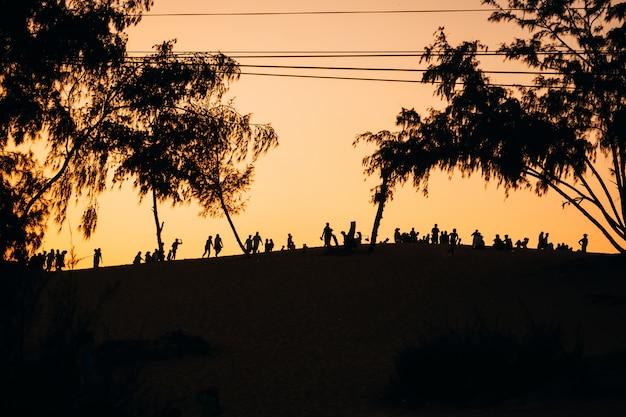 Schattenbild einer gruppe von personenenfreunden, die auf dem sand stillstehen