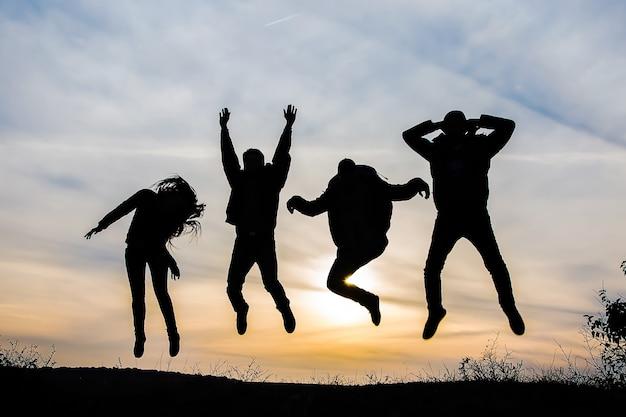 Schattenbild einer gruppe von vier glücklichen leuten, die bei sonnenuntergang springen