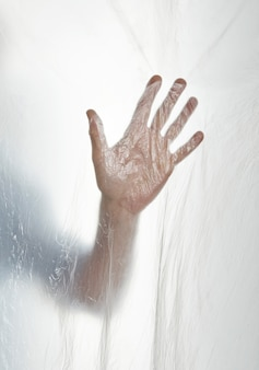 Schattenbild einer hand hinter einem transparenten plastik