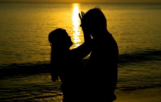 Schattenbild einer jungen braut und des bräutigams im strand auf sonnenunterganghintergrund