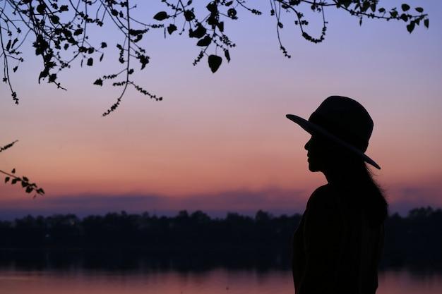Schattenbild einer jungen frau gegen schöne purpurrote farbe des abendhimmels