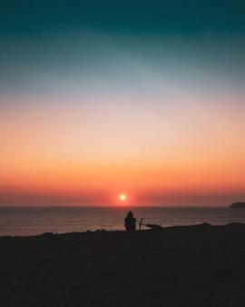Schattenbild einer person, die am ufer während des sonnenuntergangs sitzt