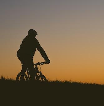 Schattenbild einer person, die ein fahrrad auf einem feld während eines sonnenuntergangs reitet