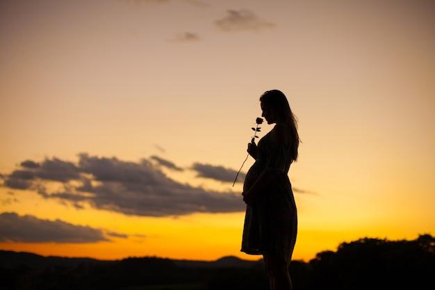 Schattenbild einer schwangeren frau, die eine rose auf sonnenuntergang riecht