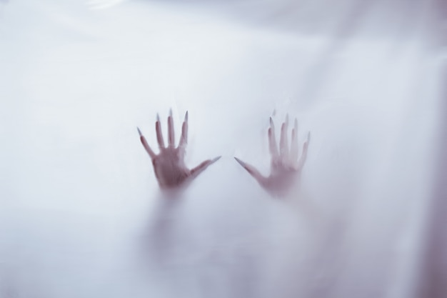 Schattenbild einer weiblichen sexuellen zahl hinter nebeligem glas. konzept des geistes des poltergeists von der anderen welt. erschreckende hände des todes durch den stoff.