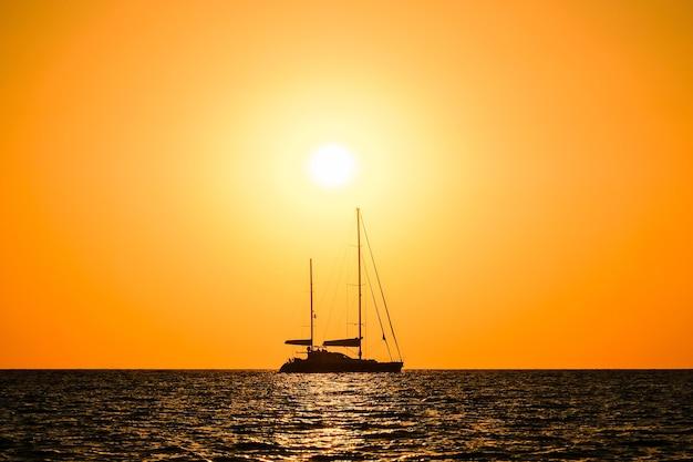 Schattenbild einer zweimastigen yacht auf see am horizonthintergrund der untergehenden sonne.
