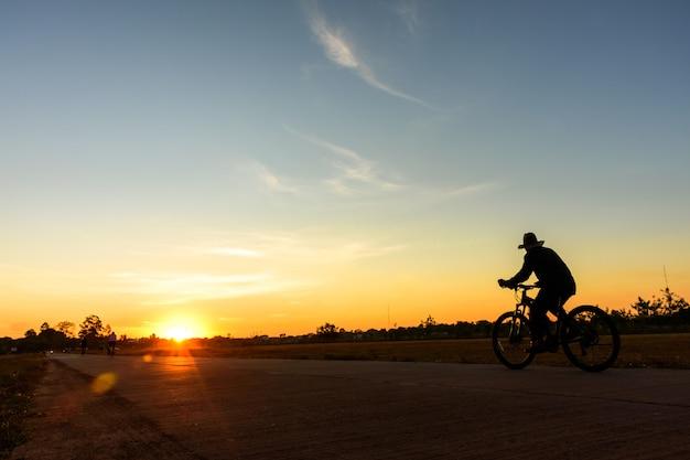 Schattenbild eines alten mannes, der öffentlich fahrrad am park des sonnenuntergangs fährt orange blauer himmel auf hintergrund.