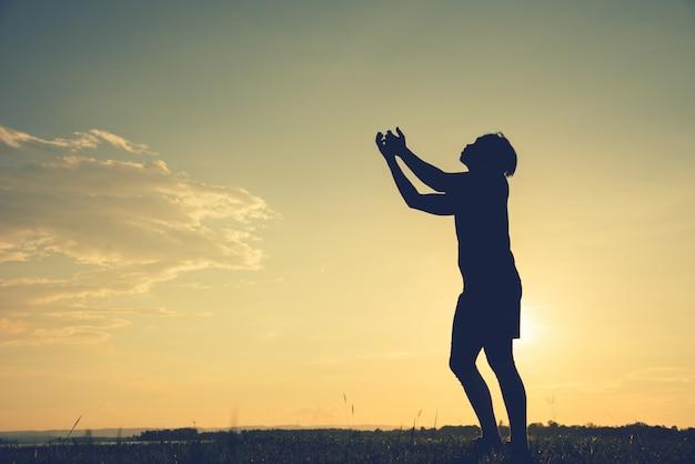 Schattenbild eines asiatischen mannes fistet oben am sonnenunterganghintergrund