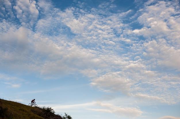 Schattenbild eines cross country-radfahrers, der abwärts geht