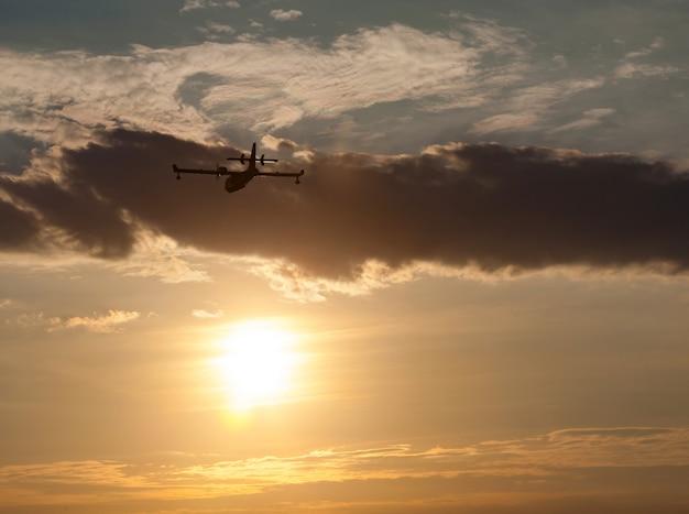 Schattenbild eines flugzeuges bei sonnenuntergang.