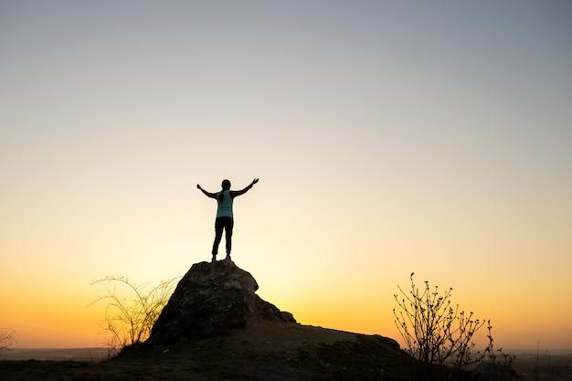 Schattenbild eines frauenwanderers, der allein auf großem stein bei sonnenuntergang in den bergen steht. weibliche touristin, die ihre hände auf hohem felsen in der abendnatur erhebt. konzept für tourismus, reisen und gesunden lebensstil.