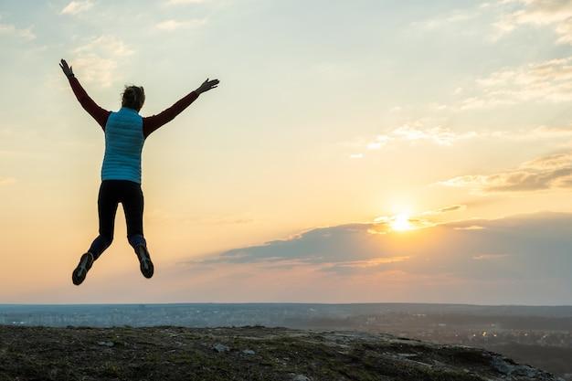 Schattenbild eines frauenwanderers, der allein auf leerem feld bei sonnenuntergang in den bergen springt. touristin, die ihre hände in der abendnatur erhebt. konzept für tourismus, reisen und gesunden lebensstil.
