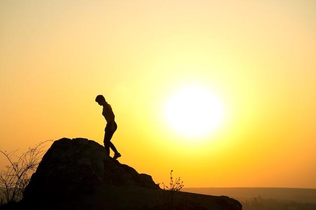 Schattenbild eines frauenwanderers, der einen großen stein bei sonnenuntergang in den bergen klettert