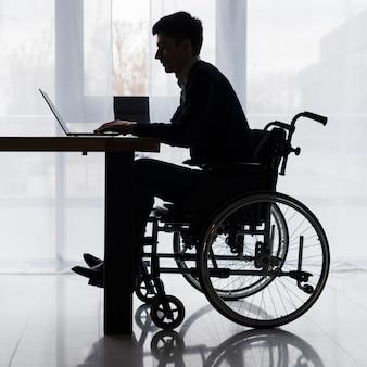 Schattenbild eines geschäftsmannes, der auf rollstuhl unter verwendung des laptops auf tabelle sitzt