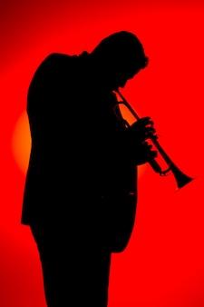 Schattenbild eines jazzmusikers, der trompete, isolat spielt