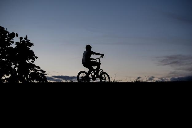 Schattenbild eines jungen, der fahrrad fährt