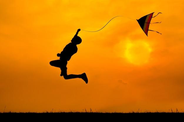 Schattenbild eines jungen, der mit dem drachen springt, um zu fliegen