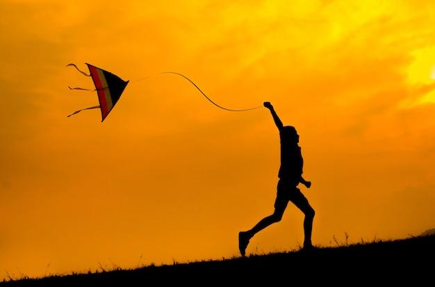 Schattenbild eines jungen, der mit drachen fliegt, um zu fliegen. sonnenuntergang.