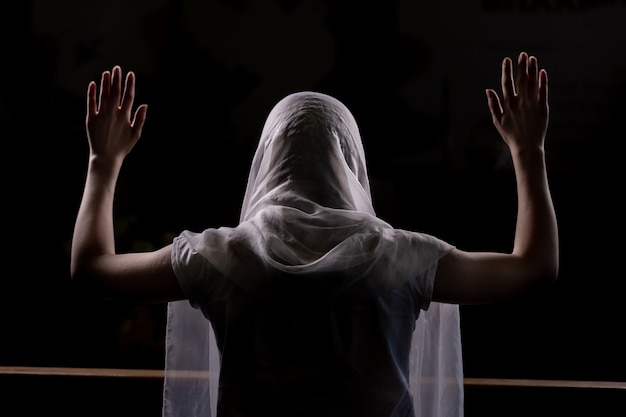 Schattenbild eines jungen mädchens, das in der kirche sitzt und mit den händen oben angehoben betet. großaufnahme von hinten. hintergrundbeleuchtung