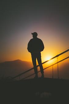 Schattenbild eines jungen mannes, der auf der treppe hinter treppengeländern mit schönem sonnenuntergangblick steht