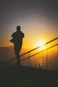 Schattenbild eines jungen mannes, der auf der treppe hinter treppengeländern mit schönem sonnenuntergangsblick geht