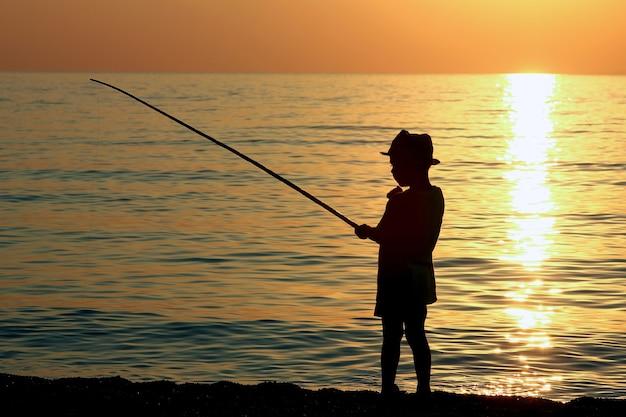 Schattenbild eines jungen mit einer angelrute auf see