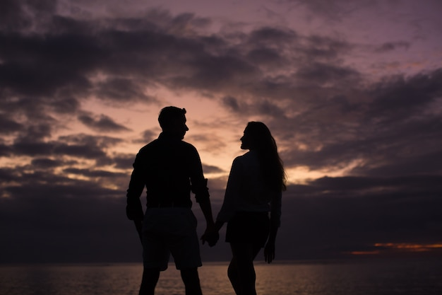 Schattenbild eines jungen paares bei sonnenuntergang am strand nahe dem ozean