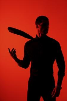 Schattenbild eines jungen selbstbewussten gutaussehenden geschäftsmannes, der schwarzes hemd im roten licht trägt