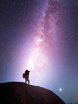 Schattenbild eines kameramädchens, das eine milchstraße schießt