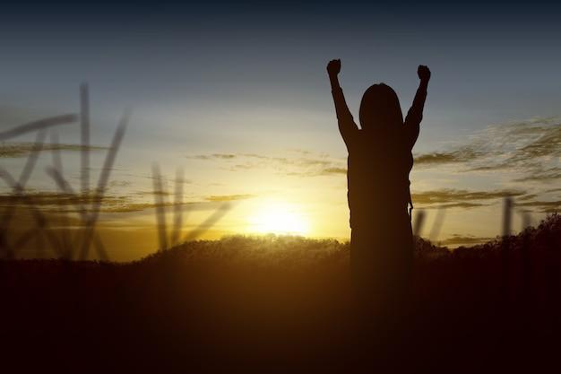 Schattenbild eines kleinen mädchens mit einem rucksack mit glücklichem ausdruck mit sonnenuntergang