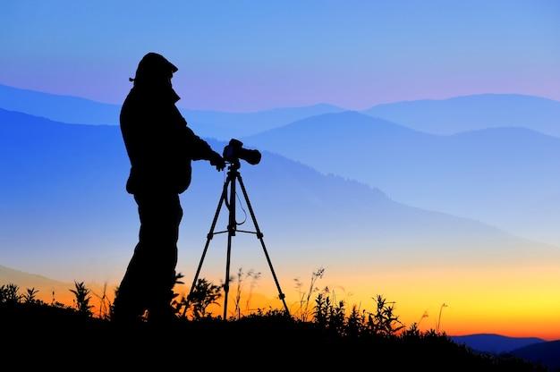 Schattenbild eines landschaftsfotografen in der dämmerung