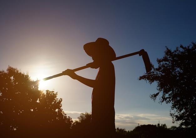 Schattenbild eines landwirts mit sonnenuntergang in der naturlandschaft