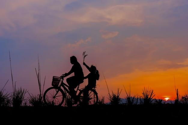 Schattenbild eines mädchens, das auf eine spur mit seinem fahrrad reitet.