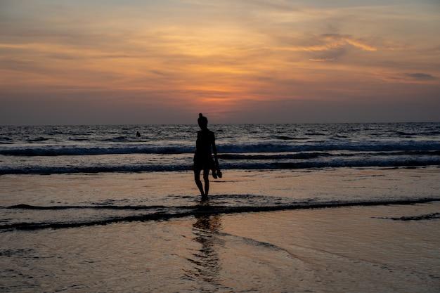Schattenbild eines mädchens, das in der hand auf das wasser auf einem strand mit ihren schuhen geht, während die sonne untergeht