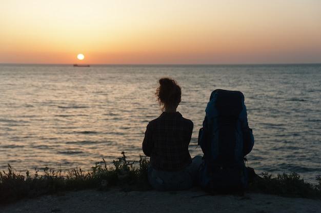 Schattenbild eines mädchens mit einem rucksack auf dem sonnenunterganghintergrund