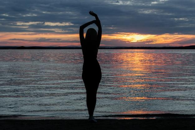 Schattenbild eines mädchens mit einer schönen figur bei sonnenuntergang am meer