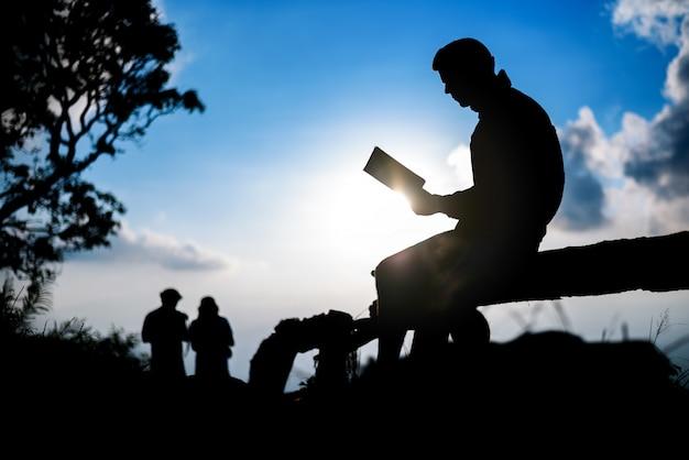 Schattenbild eines mannes, der buch auf blauer bergspitze sitzt und liest
