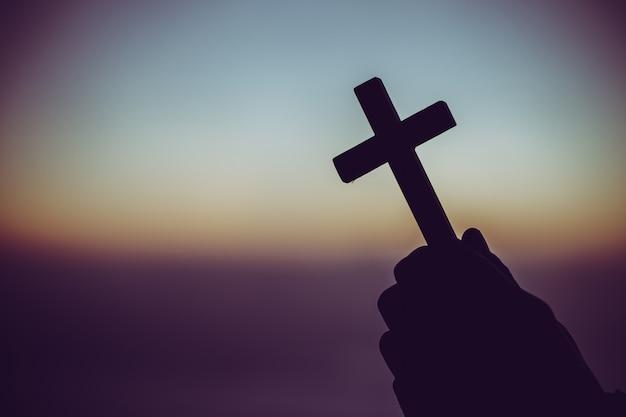 Schattenbild eines mannes, der in der hand mit einem kreuz bei sonnenaufgang betet.