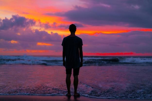 Schattenbild eines mannes gegen den hintergrund eines hellen schönen farbigen sonnenuntergangs auf dem ozean