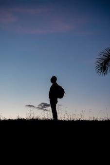 Schattenbild eines mannes im profil mit rucksack herein hinten draußen