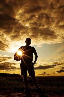 Schattenbild eines mannes mit einer kugel.
