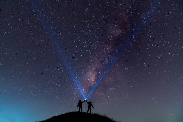 Schattenbild eines mannes mit einer taschenlampe, schönen, breiten blauen nächtlichen himmel mit sternen und milchstraßegalaxie beobachtend. astronomie, orientierung, klarer himmel