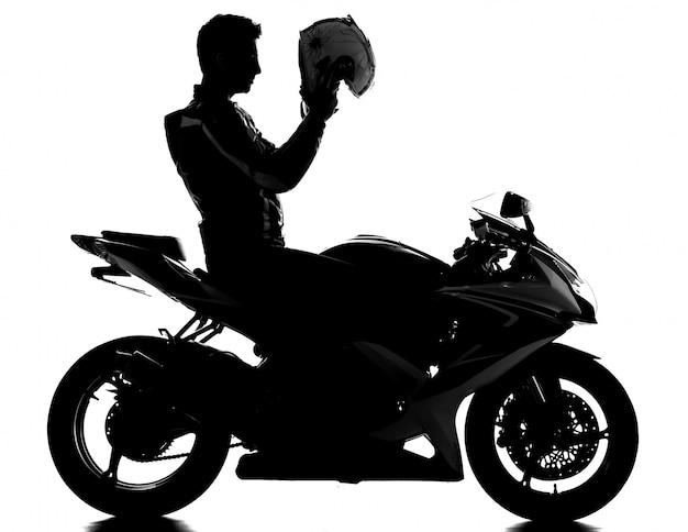 Schattenbild eines motorradrennfahrers mit sturzhelm.