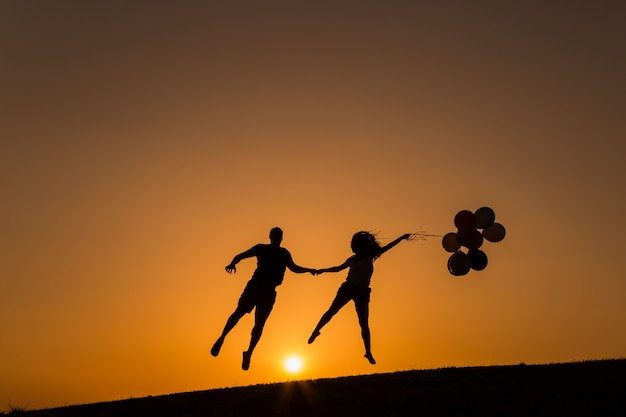 Schattenbild eines paares, das mit luftballons bei sonnenuntergang spielt