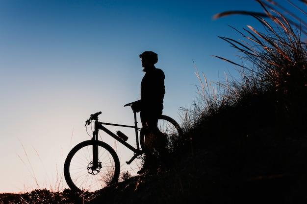 Schattenbild eines radfahrers, der das fahrrad hinunter rocky hill bei sonnenuntergang reitet. extremsport-konzept.