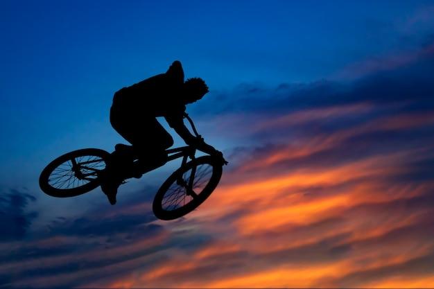 Schattenbild eines radfahrers, der gegen den schönen himmel bei sonnenuntergang springt