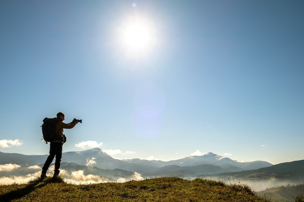 Schattenbild eines rucksacktouristenfotografen, der bilder der morgenlandschaft im herbstgebirge mit digitalkamera macht.