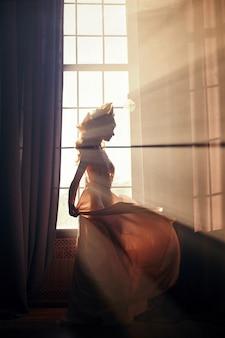 Schattenbild eines sexy frauenmädchens nahe der abendsonne des fensters morgens. mode blonde frau in den strahlen der sonne. sonnenlicht fällt auf den körper einer frau. feenhaftes magisches licht im fenster